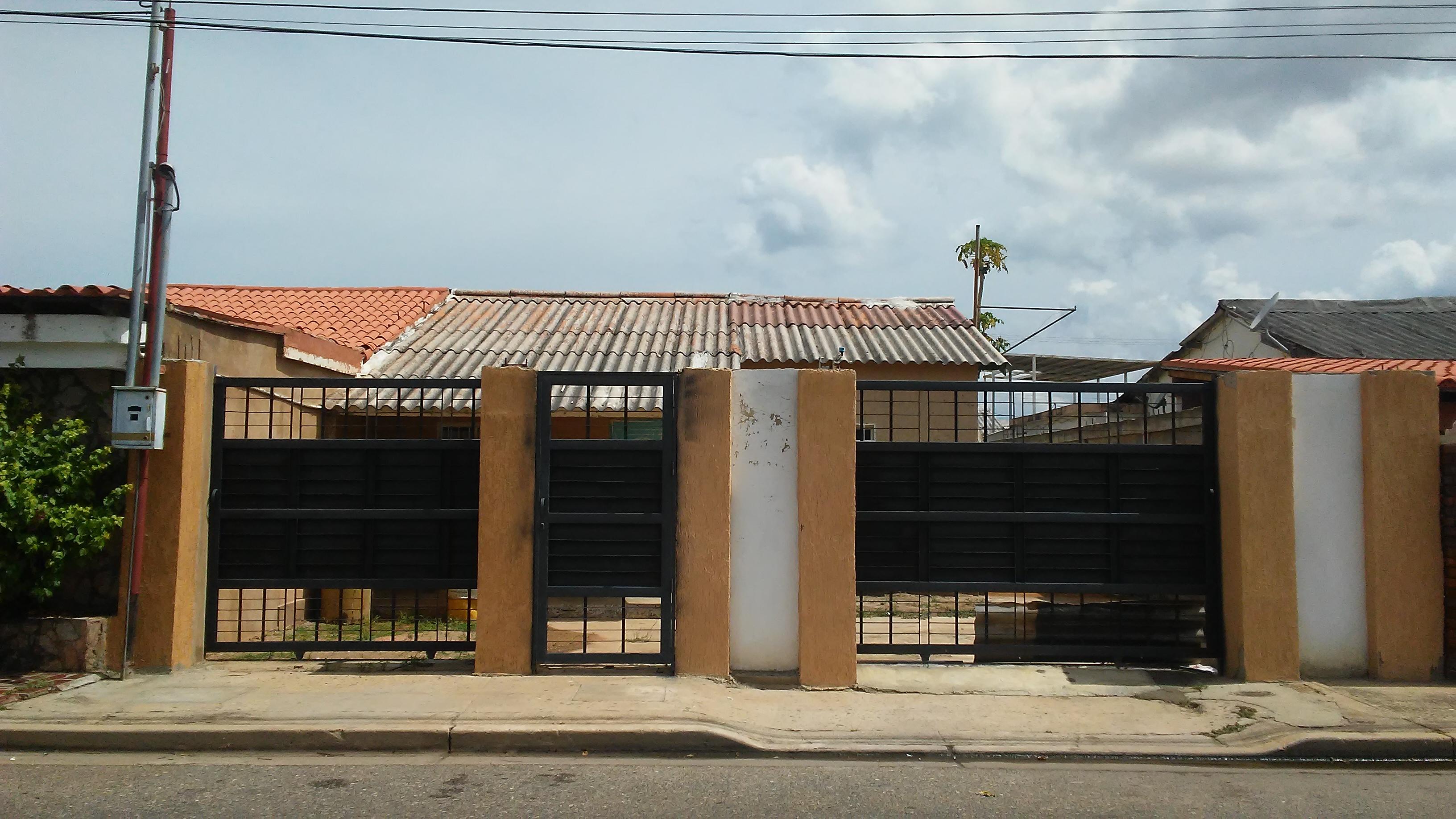 Terreno cercado con construcción de vivienda